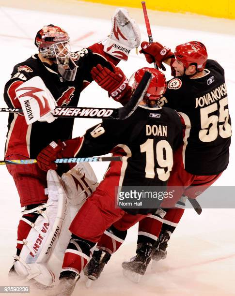 Shane Doan and Ed Jovanovski of the Phoenix Coyotes come in to celebrate with Ilya Bryzgalov after a shootout victory over the Anaheim Ducks on...