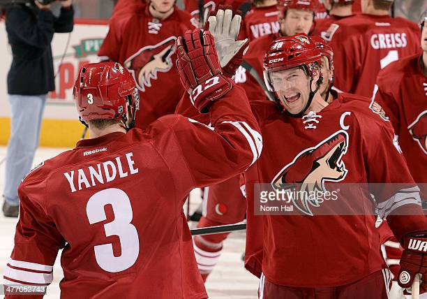 Shane Doan and Keith Yandle of the Phoenix Coyotes celebrate their 52 victory against the Montreal Canadiens at Jobingcom Arena on March 6 2014 in...