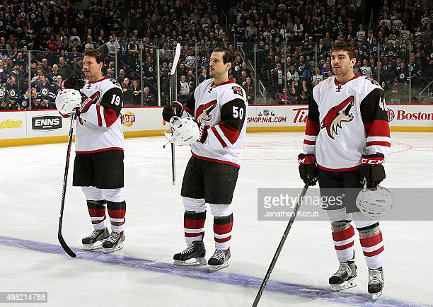 Shane Doan Antoine Vermette and Jordan Martinook of the Arizona Coyotes stand on the ice during the playing of the National anthems prior to NHL...
