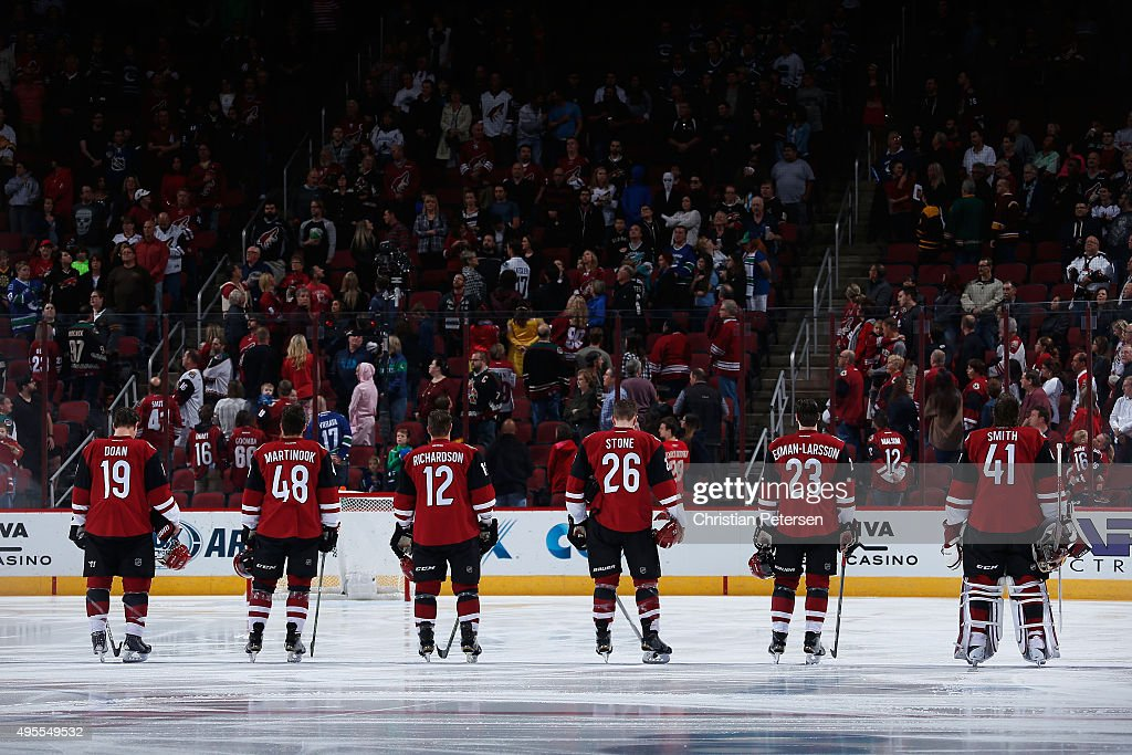 Shane Doan #19, Jordan Martinook #48, Brad Richardson #12, Michael Stone #26, Oliver Ekman-Larsson #23 and goaltender Mike Smith #41 of the Arizona Coyotes stand attended for the national anthem during the NHL game against the Vancouver Canucks at Gila River Arena on October 30, 2015 in Glendale, Arizona.