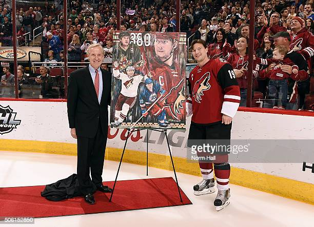 Shane Doan of the Arizona Coyotes and Executive Vice President and General Manager Don Maloney pose with a painting during a ceremony celebrating...