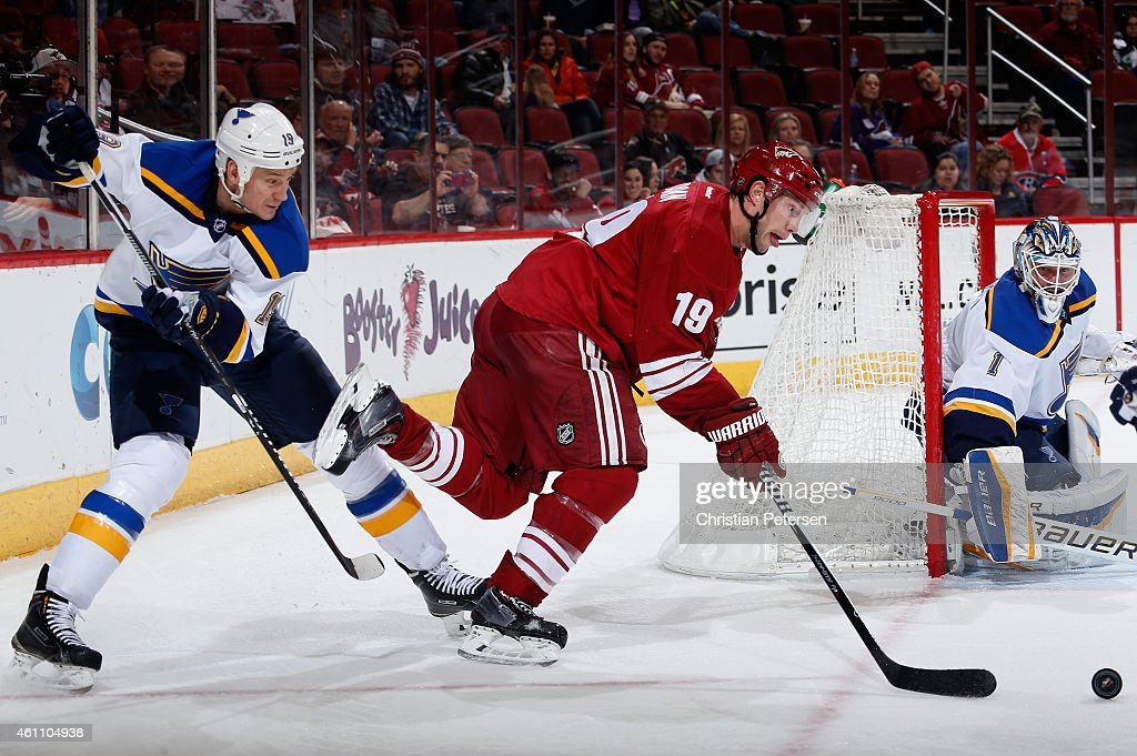 Shane Doan #19 of the Arizona Coyotes attempts to control the puck under pressure from Jay Bouwmeester #19 of the St. Louis Blues during the third period of the NHL game at Gila River Arena on January 6, 2015 in Glendale, Arizona. The Blues defeated the Coyotes 6-0.