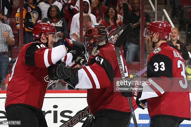 Shane Doan of the Arizona Coyotes celebrates with goaltender Mike Smith and Alex Goligoski after defeating the San Jose Sharks in the NHL game at...
