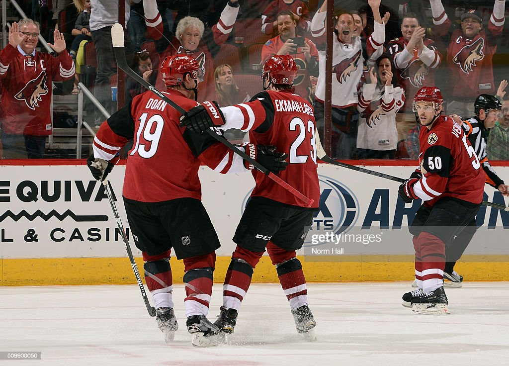 Shane Doan #19 of the Arizona Coyotes celebrates with teammate Oliver Ekman-Larsson #23 after his third period goal against the Calgary Flames as Antoine Vermette #50 of the Coyotes looks on at Gila River Arena on February 12, 2016 in Glendale, Arizona. Doan had two goals and an assist in the game which made him the all time franchise leader in points and power play goals.