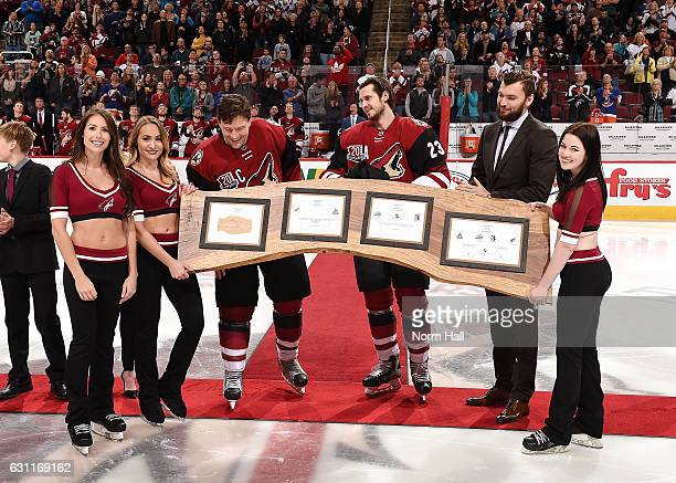 Shane Doan of the Arizona Coyotes is presented a gift in honor of his 1500 NHL games played and 400 career goals by teammates Oliver EkmanLarsson and...