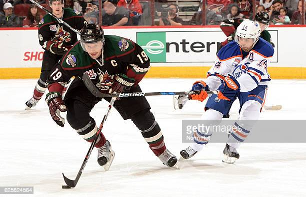 Shane Doan of the Arizona Coyotes skates the puck up ice while fighting off a stick check by Jordan Eberle of the Edmonton Oilers during the second...