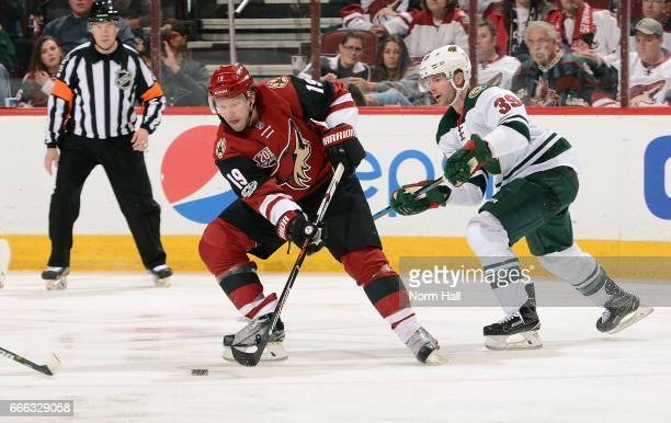 Shane Doan of the Arizona Coyotes skates with the puck ahead of Nate Prosser of the Minnesota Wild during the third period at Gila River Arena on...