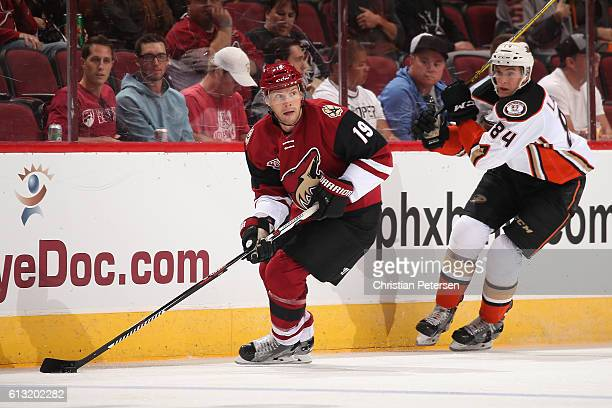 Shane Doan of the Arizona Coyotes skates with the puck during the preseason NHL game against Anaheim Ducks at Gila River Arena on October 1 2016 in...