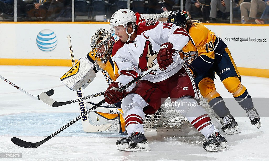 Shane Doan #19 of the Arizona Coyotes tries a backhand shot against Pekka Rinne #35 of the Nashville Predators at Bridgestone Arena on October 21, 2014 in Nashville, Tennessee.