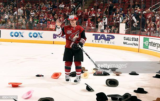 Shane Doan of the Arizona Coyotes waves to the crowd as he skates through hats thrown on the ice in recognition of his 1500th career NHL game before...