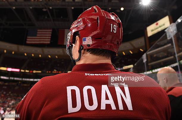 Shane Doan of the Arizona Coyotes wears an american flag sticker on his helmet as he looks on from the bench against the Winnipeg Jets at Gila River...