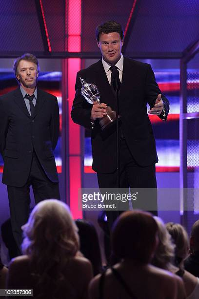 Shane Doan of the Phoenix Coyotes accepts the King Clancy Memorial Trophy as presenter Jerry Bruckheimer looks on during the 2010 NHL Awards at the...