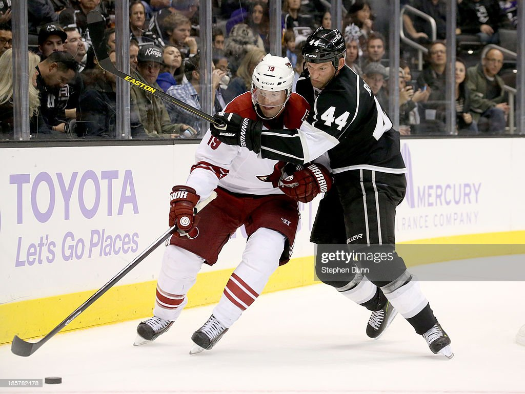 Shane Doan #19 of the Phoenix Coyotes and Robyn Regehr #44 of the Los Angeles Kings fight for the puck at Staples Center on October 24, 2013 in Los Angeles, California. The Kings won 7-4.