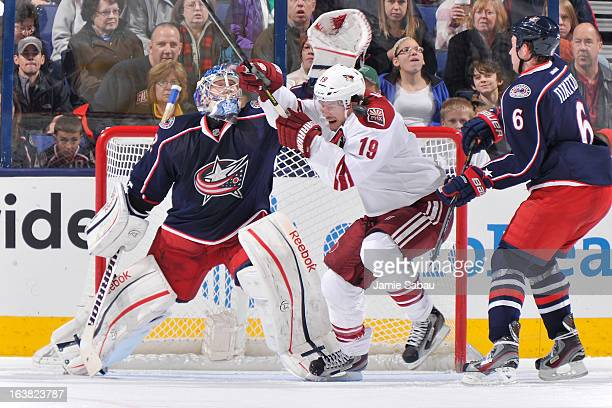 Shane Doan of the Phoenix Coyotes is hit by a shot while skating in front of goaltender Sergei Bobrovsky of the Columbus Blue Jackets during the...