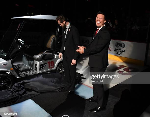 Shane Doan smiles as Oliver EkmanLarsson of the Arizona Coyotes gives him a golf cart during a pregame ceremony to honor Shane Doan and retire his...