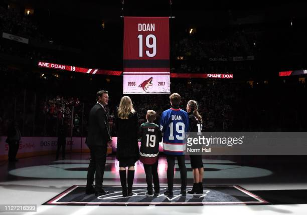 Shane Doan wife Andrea and kids Josh Carson and Karys observe as a 'Doan 19' banner is raised during a pregame ceremony before the game between the...