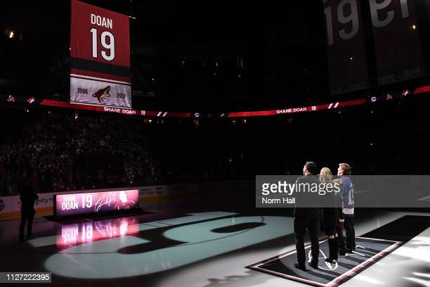 Shane Doan wife Andrea and kids Josh Carson and Karys watch as a 'Doan 19' banner is raised during a pregame ceremony before the game between the...