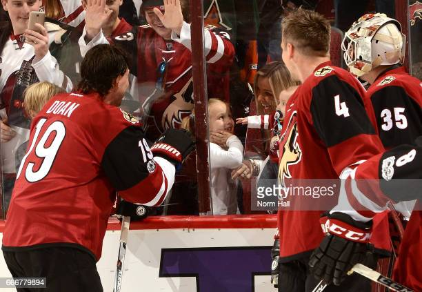 Shane Doan Zbynek Michalek and Louis Domingue of the Arizona Coyotes wave to a young fan during pregame against the Minnesota Wild at Gila River...