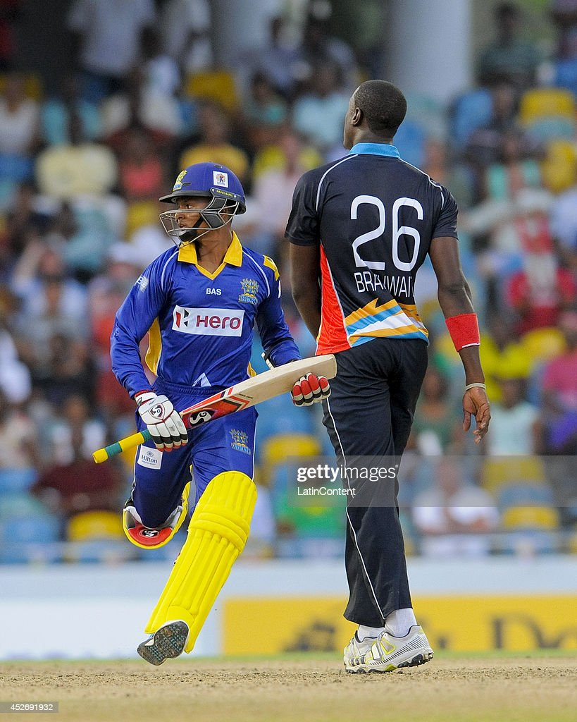Shane Dowrich (L) of Barbados Tridents runs off as Carlos Brathwaite (R) of Antigua Hawksbills looks on during a match between Barbados Tridents and Antigua Hawksbills as part of the week 3 of Caribbean Premier League 2014 at Kensington Oval on July 25, 2014 in Bridgetown, Barbados.