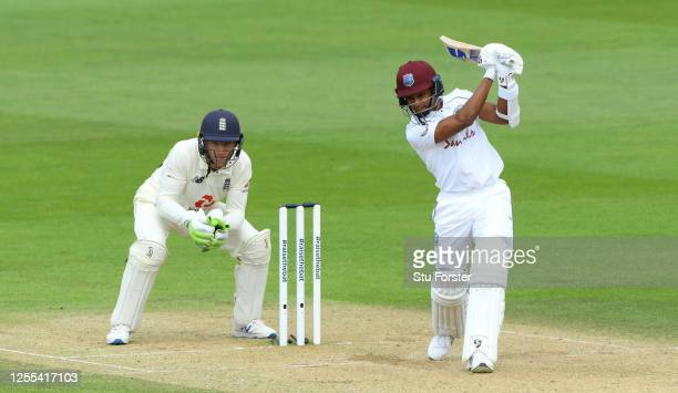 Shane Dowrich of the West Indies drives the ball as Jos Buttler of England looks on during Day Three of the 1st #RaiseTheBat Test Series between...