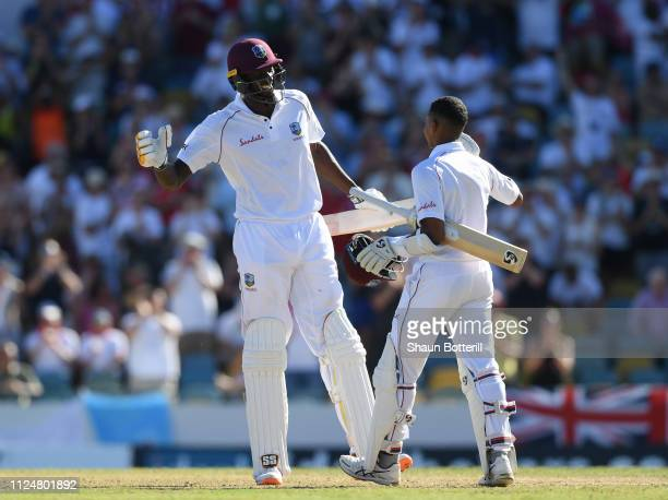 Shane Dowrich of West Indies is congratulated by captain Jason Holder after reaching his 100 during Day Three of the First Test match between England...