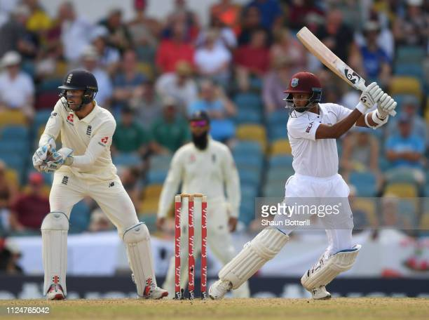 Shane Dowrich of West Indies plays a shot as Ben Foakes of England looks on during Day Three of the First Test match between England and West Indies...