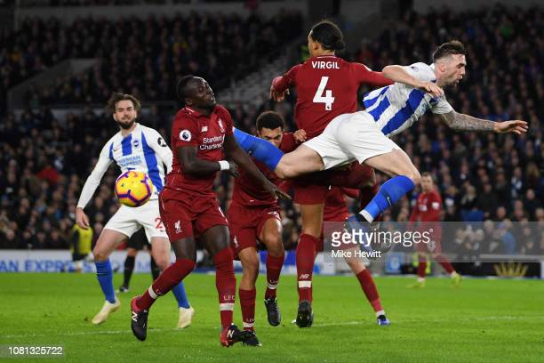 Shane Duffy of Brighton and Hove Albion clashes with Virgil van Dijk of Liverpool and Sadio Mane of Liverpool during the Premier League match between...
