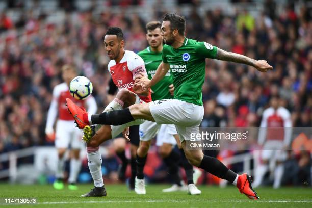 Shane Duffy of Brighton and Hove Albion is challenged by PierreEmerick Aubameyang of Arsenal during the Premier League match between Arsenal FC and...