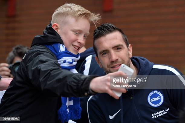 Shane Duffy of Brighton and Hove Albion takes a photo with a fan as he arrives prior to the Premier League match between Stoke City and Brighton and...