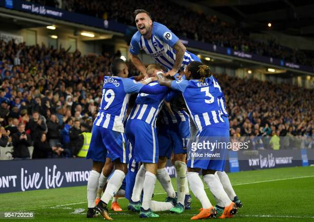 Shane Duffy of Brighton Hove Albion jumps on his teammates as they celebrate Pascal Gross scoring the opening goal during the Premier League match...