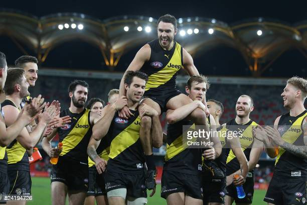 Shane Edwards of the Tigers is chaired from the field after his 200th match during the round 19 AFL match between the Gold Coast Suns and the...
