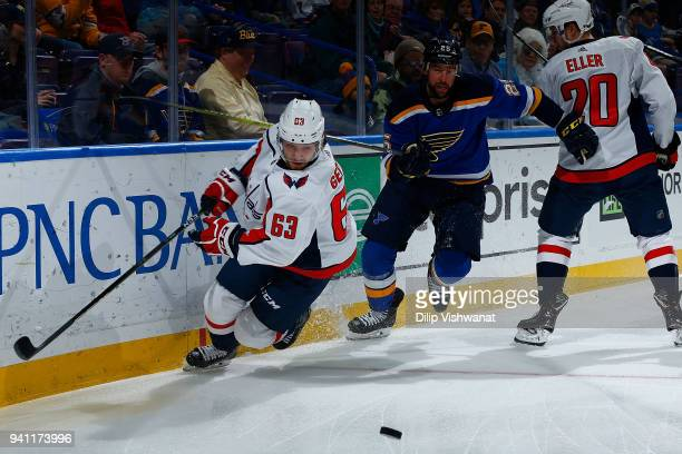 Shane Gersich of the Washington Capitals looks to beat Chris Butler of the St Louis Blues to the puck at Scottrade Center on April 2 2018 in St Louis...