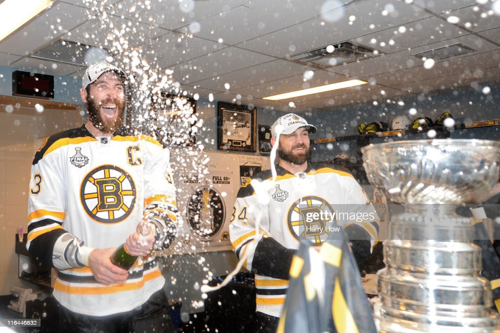 Shane Hnidy #34 and Zdeno Chara #33 of the Boston Bruins celebrate in the locker room after defeating the Vancouver Canucks in Game Seven of the 2011 NHL Stanley Cup Final at Rogers Arena on June 15, 2011 in Vancouver, British Columbia, Canada. The Boston Bruins defeated the Vancouver Canucks 4 to 0.