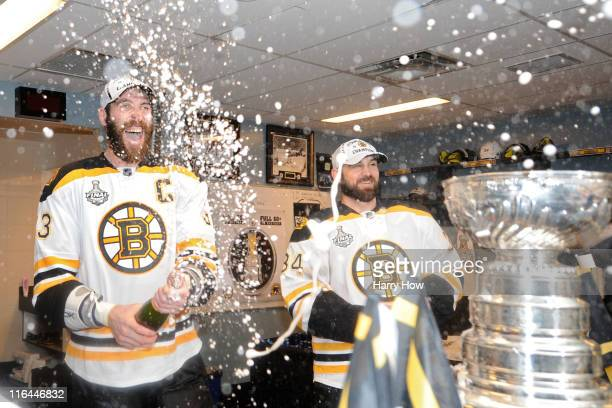 Shane Hnidy and Zdeno Chara of the Boston Bruins celebrate in the locker room after defeating the Vancouver Canucks in Game Seven of the 2011 NHL...