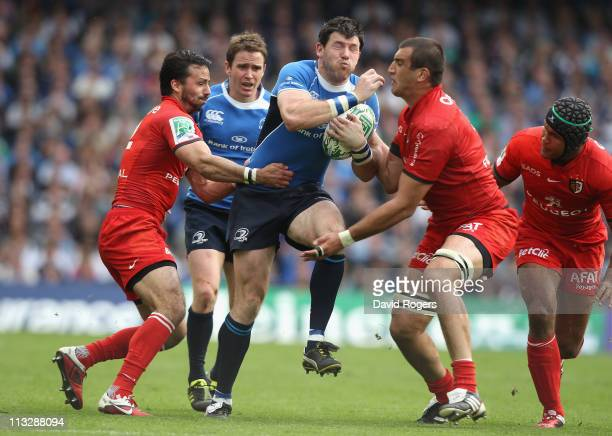 Shane Horgan of Leinster charges past Yoann Maestri and Clement Poitrenaud during the Heineken Cup semi final match between Leinster and Toulouse at...