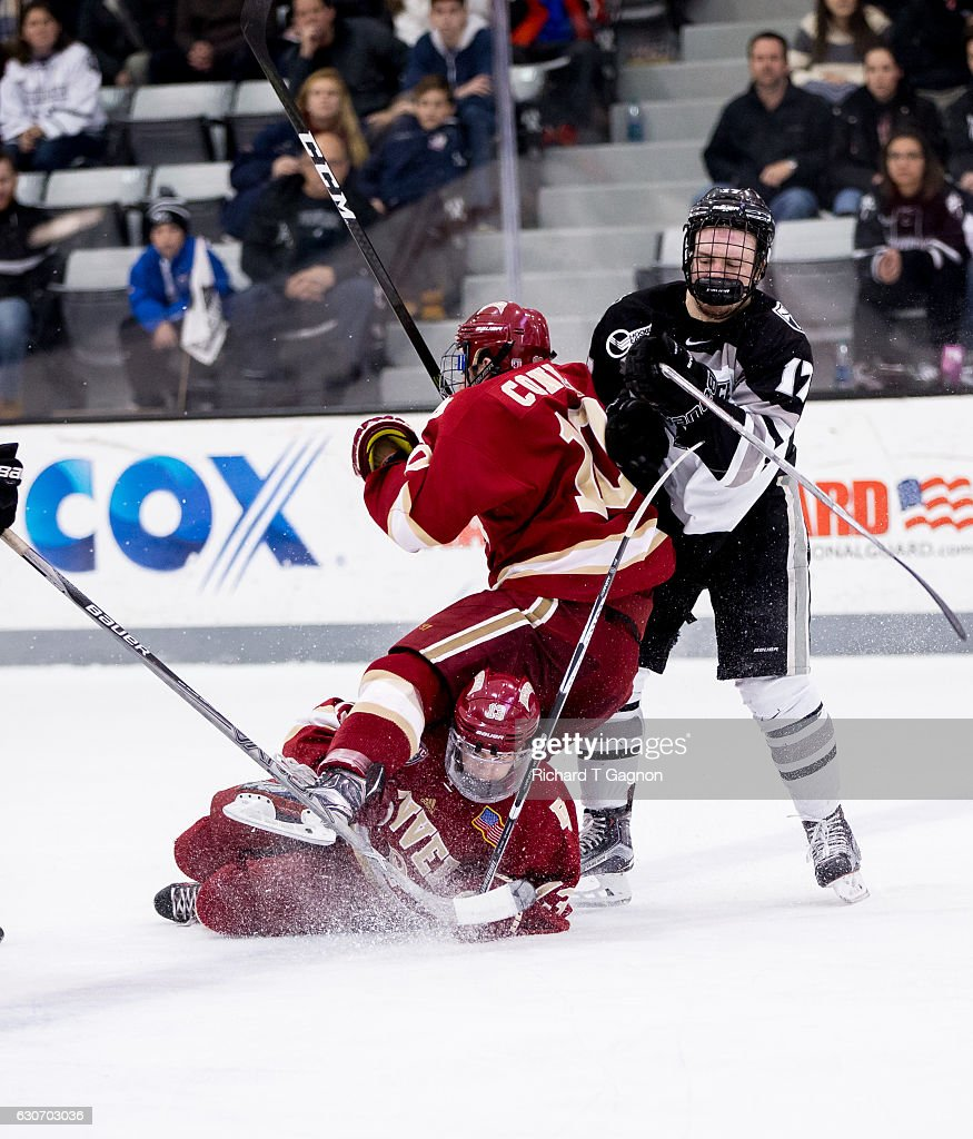 Shane Kavanagh #17 of the Providence College Friars checks both Kevin Conley #10 and Liam Finlay #13 of the Denver Pioneers during NCAA hockey at the Schneider Arena on December 30, 2016 in Providence, Rhode Island. The game ended in a 2-2 tie.