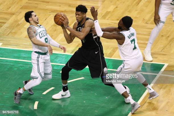 Shane Larkin of the Boston Celtics and Jaylen Brown defend Giannis Antetokounmpo of the Milwaukee Bucks in the fourth quarter of Game Two in Round...
