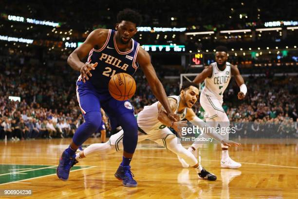 Shane Larkin of the Boston Celtics attempts to steal the ball away from Joel Embiid of the Philadelphia 76ers during the second half of their game at...