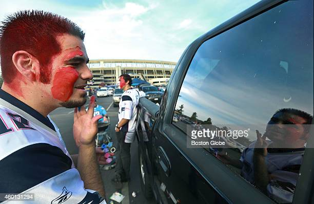 Shane Long a Patriots fan from Las Vegas uses the window of a vehicle as a mirror as he puts on his pregame red white and blue face paint The New...