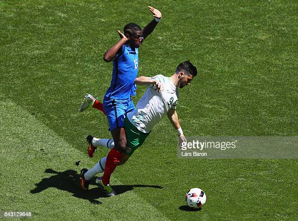 Shane Long of Republic of Ireland is challenged by Paul Pogba of France resulting in a penalty kick during the UEFA EURO 2016 round of 16 match...
