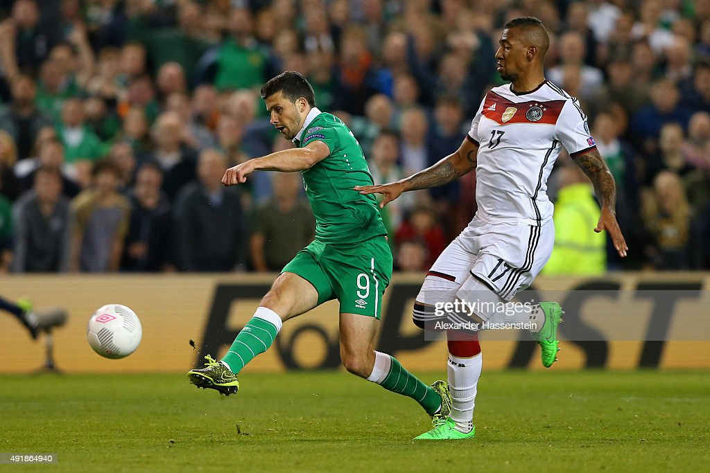 Shane Long of Republic of Ireland scores the opening goal under pressure from Jerome Boateng of Germany during the UEFA EURO 2016 Qualifier group D match between Republic of Ireland and Germany at the Aviva Stadium on October 8, 2015 in Dublin, Ireland.