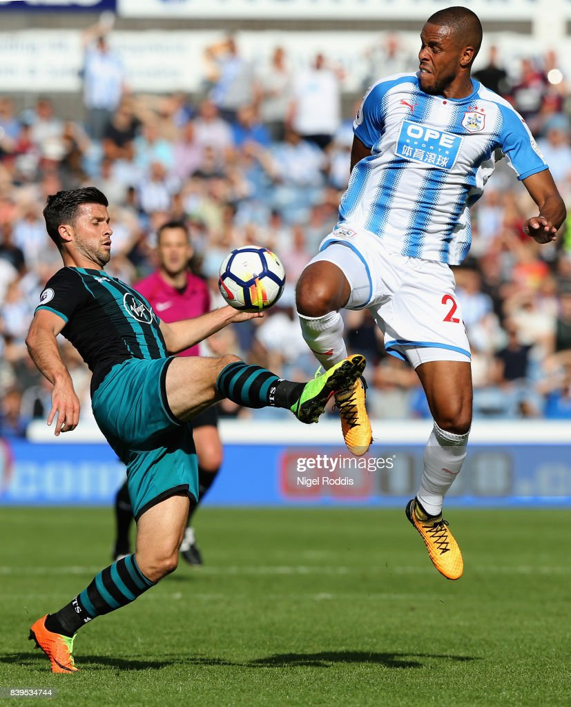 Shane Long of Southampton and Collin Quaner of Huddersfield Town battle for possession during the Premier League match between Huddersfield Town and Southampton at John Smith's Stadium on August 26, 2017 in Huddersfield, England.