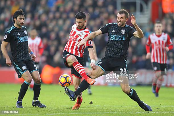 Shane Long of Southampton and Gareth McAuley of West Bromwich Albion compete for the ball during the Premier League match between Southampton and...
