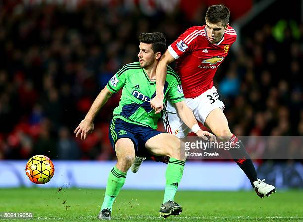 Shane Long of Southampton and Paddy McNair of Manchester United compete for the ball during the Barclays Premier League match between Manchester...