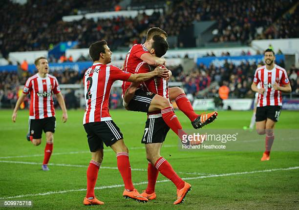 Shane Long of Southampton celebrates scoring his team's first goal with his team mates James WardProwse and Cedric Soares during the Barclays Premier...
