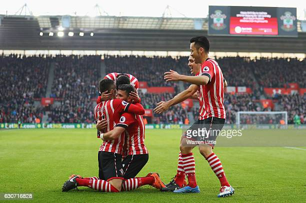 Shane Long of Southampton celebrates scoring the opening goal with his team mates including Dusan Tadic during the Premier League match between...