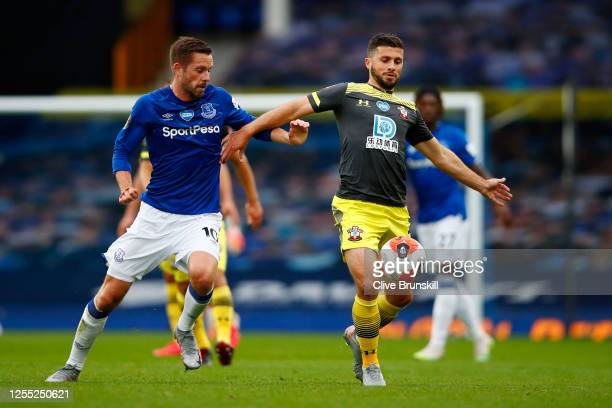 Shane Long of Southampton controls the ball while under pressure from Gylfi Sigurdsson of Everton during the Premier League match between Everton FC...