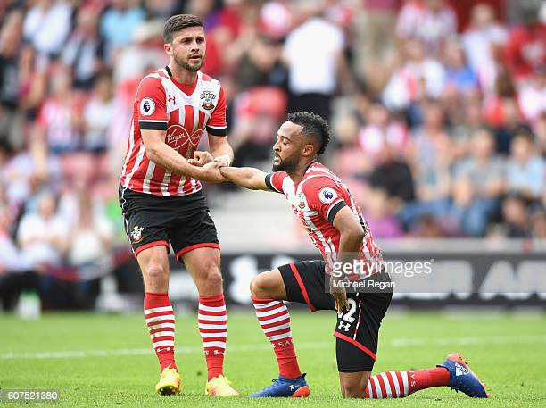 Shane Long of Southampton helps Nathan Redmond of Southampton up after missing a chance during the Premier League match between Southampton and...