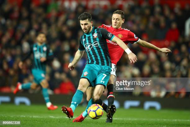Shane Long of Southampton holds off Nemanja Matic of Manchester United during the Premier League match between Manchester United and Southampton at...