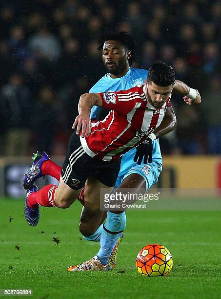 Shane Long of Southampton is challenged by Alexandre Song of West Ham United during the Barclays Premier League match between Southampton and West...